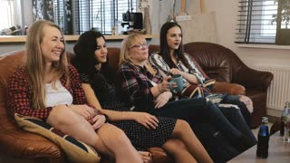 European girls watch funny sitcom episode on TV. Female friends smile and discuss emotion romantic movie 4K slow motion.
