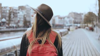 European lady tourist walks near river with phone. Pretty traveler female looks around walking along a river quay. 4K.