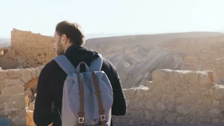 European man explores ancient mountain scenery. Young male tourist with camera and backpack takes photos. Israel 4K.
