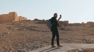 European man walks to ancient ruins, looks around. Relaxed male tourist makes phone videos on desert road. Israel 4K.