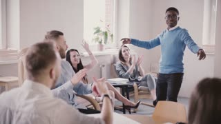 Excited African American businessman celebrates victory with funny dance. Successful boss in modern office slow motion.