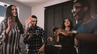 Excited African American guy dancing with multiethnic friends at casual birthday party at home slow motion panning shot.