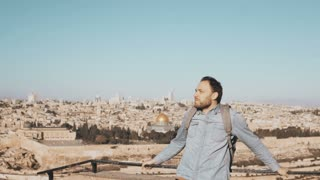 Excited European tourist male looks around. Israel, Jerusalem. Happy smiling man with backpack enjoys beautiful view 4K.