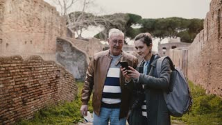 Excited happy senior man and smiling European young woman taking selfie near old ruins in Ostia, Italy on vacation trip.