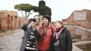 Excited happy senior tourist women and smiling European young girl taking selfie near old historic ruins in Ostia, Italy