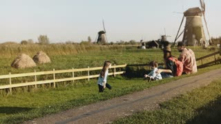 Family of four sit together near a windmill farm. Mom, dad and two kids enjoy sunny sunset countryside scenery. 4K.