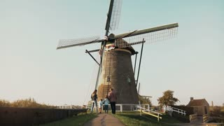 Family of four stand by huge old Dutch wind mill. Amazing shot of people before an architecture landmark. Back view. 4K.
