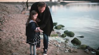 Father and daughter on the shore, little girl throw stone into the water. Man show to girl how play stone skipping.