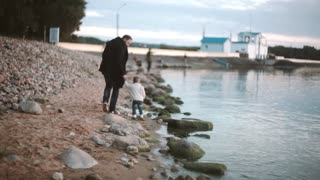 Father and son on beach holding hands and walking along the shore at sunset. Girl running to man. Father hugs daughter.