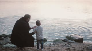 Father and son on the shore, little boy throw stone into the water. Man squatting and show boy how play stone skipping.