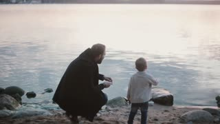Father and son on the shore talking. Man squatting and show boy how to play stone skipping. Little boy jumping for joy.