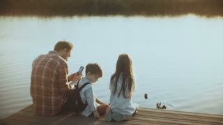Father and two kids sit together on a lake pier. European man with children photographs water birds with smartphone. 4K.
