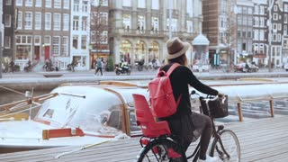 Female blogger rides bicycle along a river quay. Tourism. Caucasian girl in hat on a city bike. Side view slow motion.