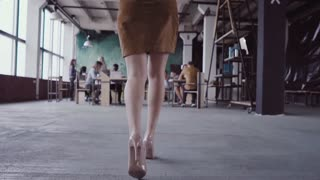 Female blonde team leader walking through office and controls work of employee. Female looks the fabric examples slow mo