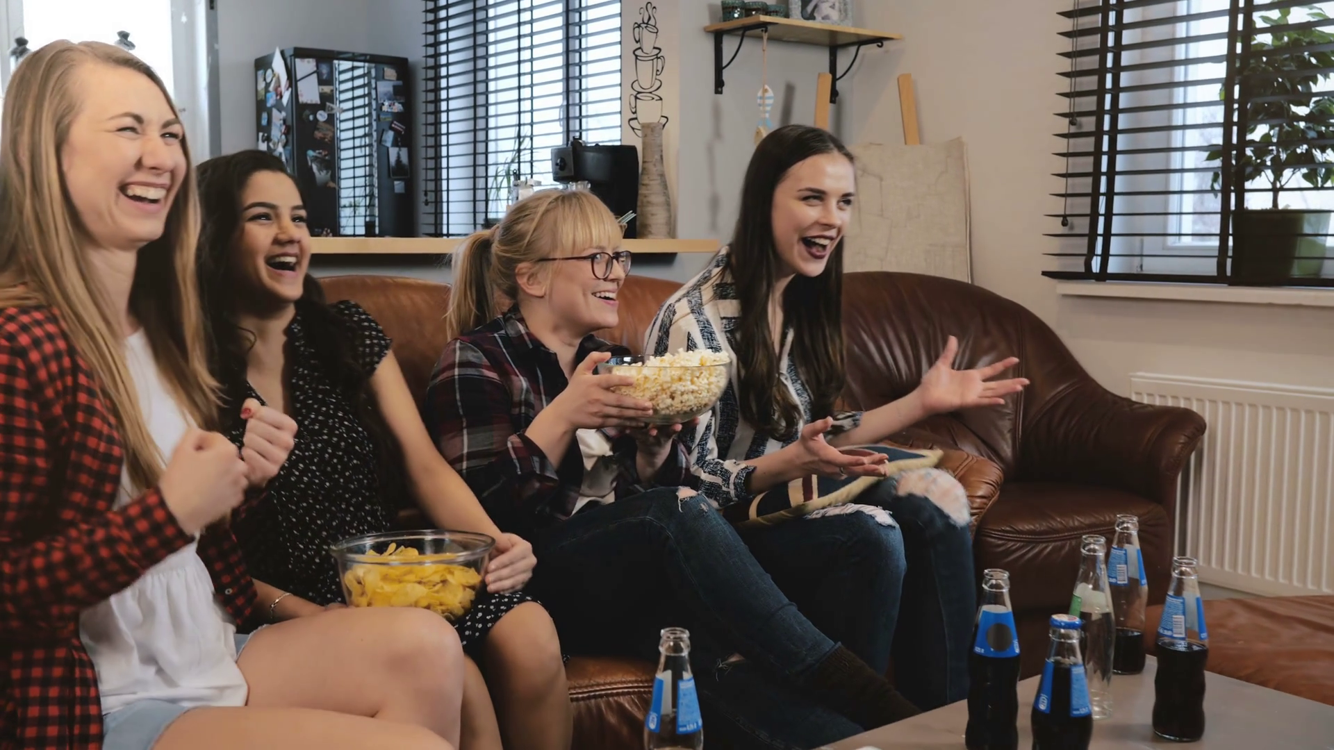 Female friends watch comedy film at home on TV. Happy ...