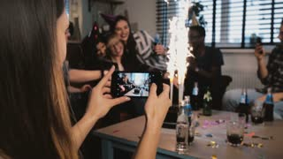 Female hands take a smartphone picture of multiethnic birthday party with firework candles, friends hugging slow motion.