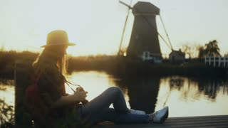 Female photographer sits on a sunset lake pier. Girl with camera takes a photo of traditional old rustic windmill. 4K.