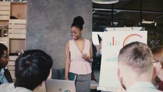 Female team leader explaining data on flip chart. Modern multiethnic financial business meeting in trendy coworking 4K.