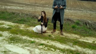 Film crew launches drone at the field. Man operating the copter, woman shoots on camera. Aerial view of the countryside.