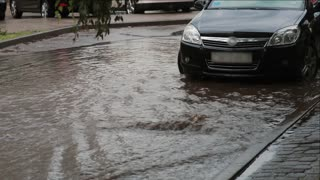 Flooding water on a pavement after heavy rain with sound. Car is near, people walk by.