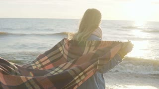 Freedom: young woman standing on shore of sea and raises hand up with plaid. Happy female on beach on cold windy day.