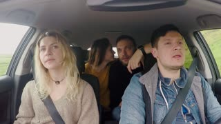 Friends traveling by car together and listening the music. Group of young people dancing, having fun inside the vehicle.