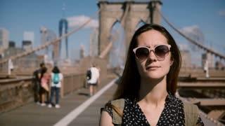 Front view of beautiful Caucasian brunette traveler woman in fashionable sunglasses enjoying walk at Brooklyn Bridge 4K.