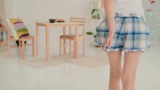 Funny young woman dancing in kitchen, running through the room wearing pajamas in the morning. Slow motion.