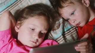 Girl and boy lying on the bed and watching cartoon on touchscreen tablet. Brother and sister having rest together.