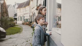 Girl and boy pointing at gifts in toy shop window. Two European kids make their wishes at store. Half timber houses. 4K.