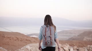 Girl at mountain top, arms wide open. Slow motion. Pretty European woman traveler excited. Happiness. Israel desert.