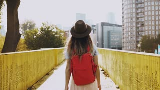 Girl in hat with long hair walks on a city bridge. Caucasian woman between yellow walls with red backpack. Back view 4K.