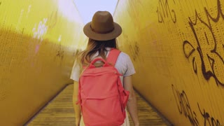 Girl in hat with red backpack walks in yellow tunnel. Woman walking between art installation bridge walls. Rotterdam. 4K