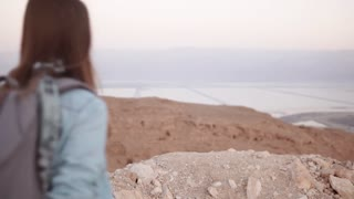 Girl near sea scenery, arms wide open. Slow motion. Pretty Caucasian woman happy and excited. Israel Dead Sea. Freedom.