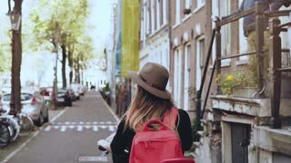 Girl on a bicycle with a red back seat. Slow motion close-up. Happy female tourist. Leisure bike ride along street.