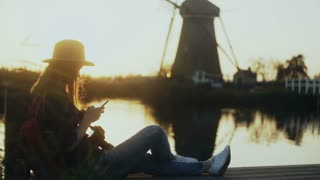 Girl sits with smartphone on sunset lake quay. Woman using mobile app outdoors. Traditional Dutch windmill scenery. 4K.