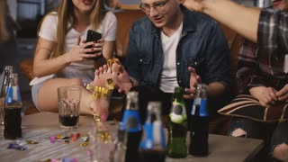 Girl takes confetti off her leg at birthday party. Diverse group of friends celebrate together, funny hats and drinks 4K