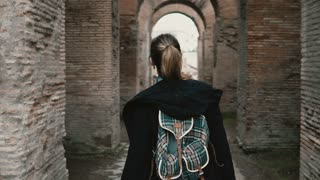 Girl tourist is walking in historical centre of Rome, Italy. Woman passing the chain of ancient arcs made of red brick.