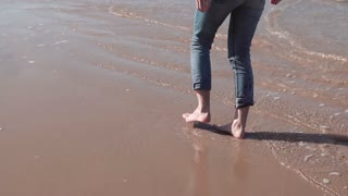 Girl walks along sea shore, throws stone in water. Freedom concept. Wind blowing in hair. Enjoying vacation. Slow motion
