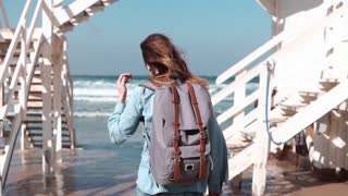 Girl walks by white stairs to sunny sea shore. Freedom. Hair blowing in wind. Woman with backpack on beach. Slow motion.