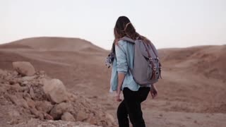 Girl walks near mountain drop. Slow motion. Young female tourist on desert canyon edge. Big rocks and stones. Israel.