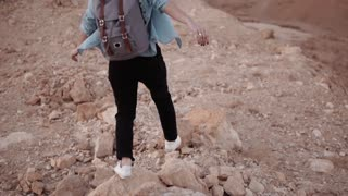 Girl walks on a desert sheer drop. Slow motion. Young woman wanders on big chasm rocks and stones. Dangerous risky path.