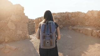 Girl with backpack explores ancient desert ruins. Pretty woman walks among mountain fortress walls in Masada, Israel. 4K