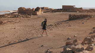 Girl with backpack explores desert ruins. Pretty European female traveler walks among ancient scenery. Masada Israel 4K.