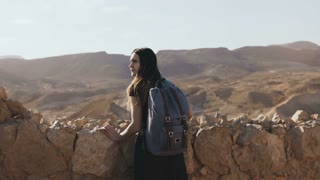 Girl with backpack looks at mountain panorama. Attractive European woman explores ancient ruins. Masada, Israel. 4K.