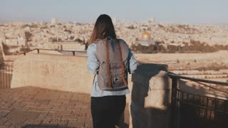 Girl with backpack walks to see old Jerusalem town. Excited European tourist raises hands joyful and happy. Israel. 4K.