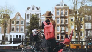 Girl with bicycle sending video to friends online. Pretty European woman blogging on social networks. Back view. 4K