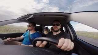 Group of young people going to the trip by car together. Happy friends filming on gopro and dancing to music.
