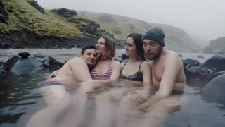 Group of young people relaxing on hot springs in mountains in Iceland. Tourists enjoying the natural spa.