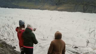 Group of young people standing on the mountain and showing to something, walking in Vatnajokull ice lagoon in Iceland.